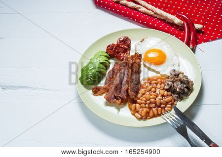 English breakfast of bacon, fried egg, beans, mushrooms, avocado and stick bread