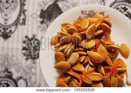 Major raw pumpkin seeds on a vintage saucer