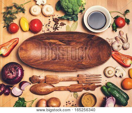 Fresh vegetables ingredients for tasty vegetarian cooking on rustic wooden background around wooden salad plate, top view. Healthy eating, diet or vegan food concept.
