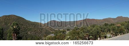 Landscape in the semi desert Little Karoo in the Republic of South Africa, mountains, barren vegetation and blue sky, panoramic