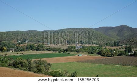 Village in the semi desert Little Karoo in the Republic of South Africa, fields and hills, houses and a church,