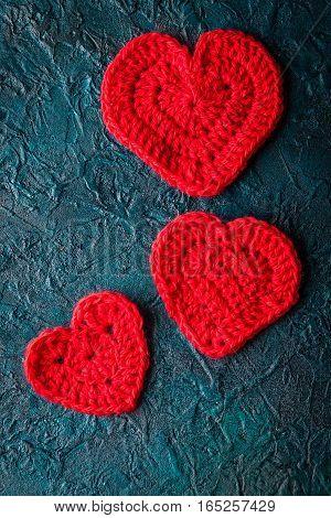 Three crochet valentine hearts on dark bacground.