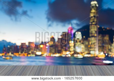 Opening wooden floor blurred bokeh lights Hong Kong city harbor with twilight sky background