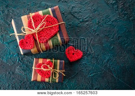 Gift boxes and crochet valentine hearts on dark bacground.