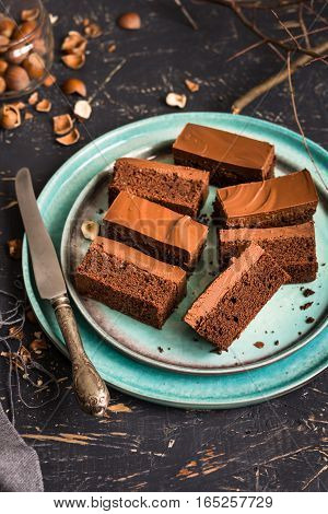 nutella, bars, dessert, sweet, brownie, cake, chocolate, cocoa, dark, frosting, ganache, rectangular, slices, blue, plate, dark, wood, board, coffee, hazelnuts, raw, whole,