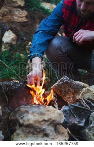 Tourist with a beard in a plaid jacket kindle a fire in the autumn forest
