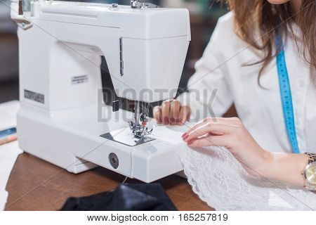 Cropped image of female tailor stitching fine lace with sewing machine sitting in dressmaking studio.