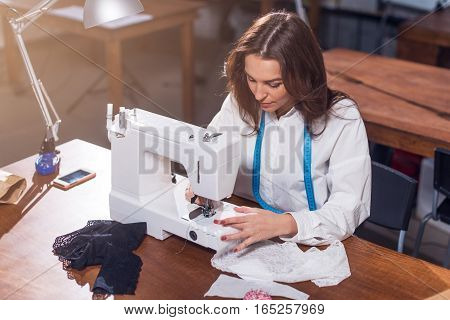 Female dressmaker working with sewing machine, stitching fabric sitting at table in studio.