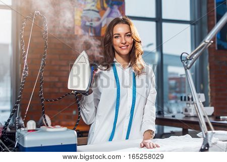 Portrait of attractive young Caucasian brunette dressmaker standing in white clothes holding steam iron in studio