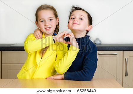 Kids (siblings boy and girl) hug and girl forms heart with hands at home in the kitchen