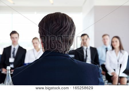 Speaker at business conference looking at audience waiting for questions