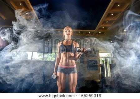 Sexy athlete blonde fitness woman in the gym workout with dumb on bicep. smoke