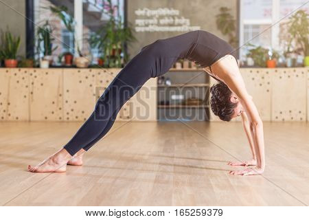 Slim flexible young woman doing yoga exercise standing in bridge position in a gym.