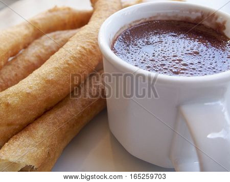 Churros con chocolate are a popular Spanish dessert. The fried churros are meant to be dipped in the rich hot chocolate.