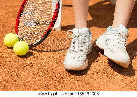 Tennis player on break focus on tennis shoes racket and balls