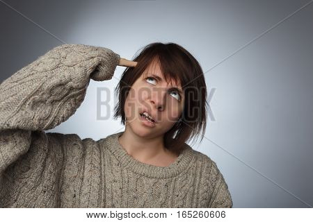 Girl wrinkles her face in disgust, putting fingers to temple