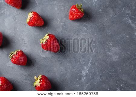 Strawberry. Fresh strawberry on dark background . Red strawberry. Loosely laid strawberries in different positions. Copyspace.