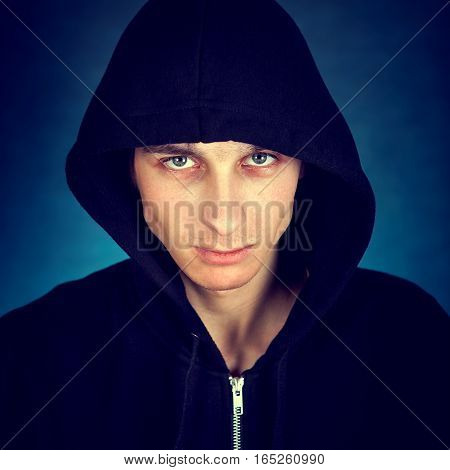 Toned Photo of Serious Young Man in the Hood on the Dark Background