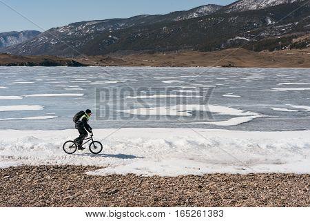 Man on BMX rides on the frozen lake, near the ice.