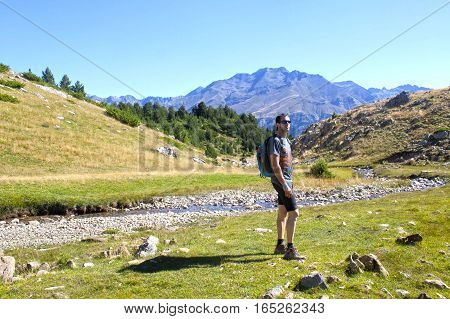 Guy Looking To The High Of A Mountain While Hiking In The Pyrenees