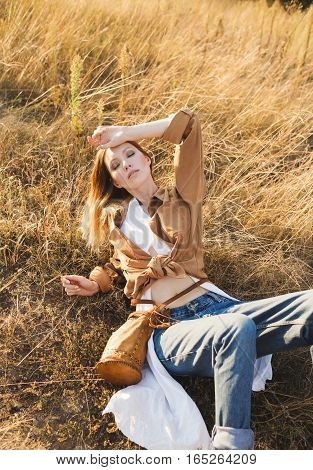 Beautiful blonde in blue jeans a white shirt and brown jacket is sitting in a field . Boho style