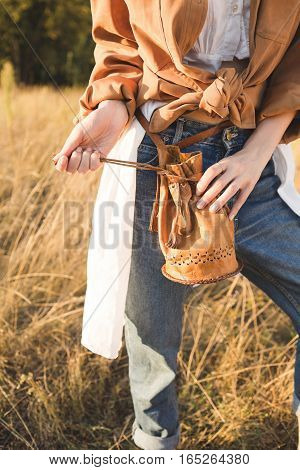 Beautiful blonde in blue jeans a white shirt and brown jacket posing in a field. Boho style