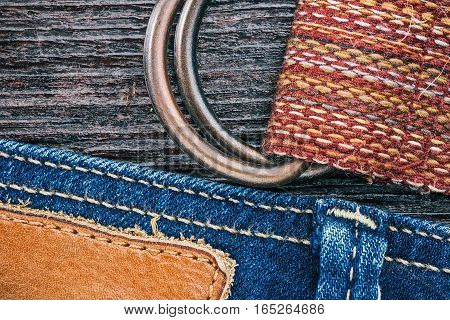 Blue jeans stitched edge and textile belt combined background. Macro view