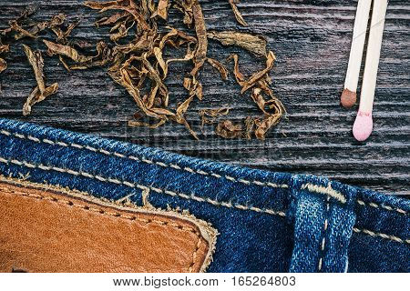 Blue jeans stitched edge, tobacco flakes and matches on wood. Macro view and Macro view and Macro view