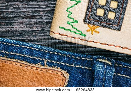 Blue jeans stitched edge, embroidered leather and dark brown wood combined background. Macro view