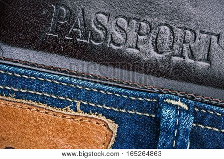 Blue jeans stitched edge and dark leather passport cover combined background. Macro view