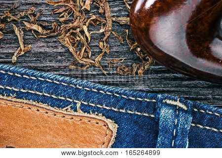 Blue jeans stitched edge, tobacco flakes and smoking pipe on wood. Macro view and Macro view
