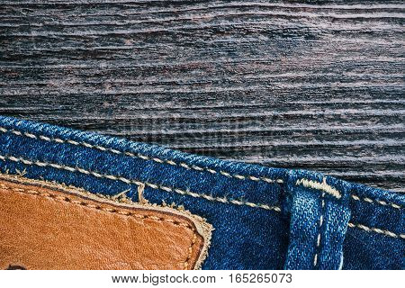 Blue jeans stitched edge and dark brown wood combined background. Macro view