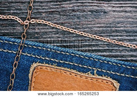 Blue jeans stitched edge and dark brown leather combined background with copper chains. Macro view