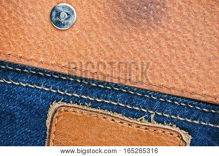 Blue jeans stitched edge and golden leather combined background. Macro view