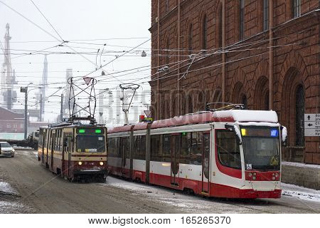 two red tram driving towards each other on the street under snow winter terracotta brick old building road machines wires rails Saint-Petersburg Russia