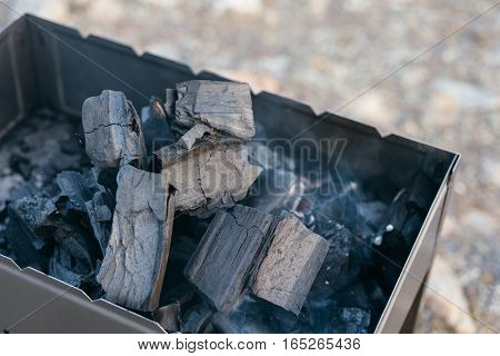 Barbecue stands on the shore of scenic Lake Baikal at sunset. It poured that burns coal. He watered the ignition a special liquid.