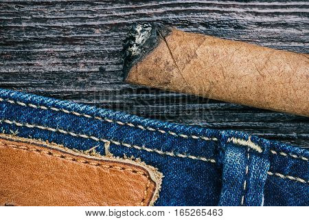 Blue jeans stitched edge and ashed cigar on wood. Macro view