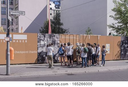 BERLIN GERMANY - AUGUST 25 2016: Tourists At Historic Checkpoint Charlie In Famous Friedrichstrasse