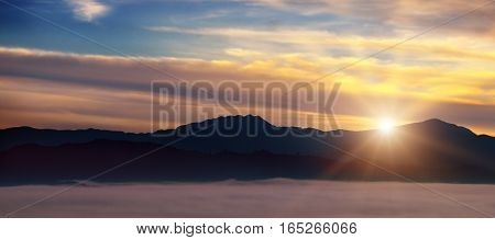Bright sunrise the mist in a mountain valley and mountain peaks on the horizon.
