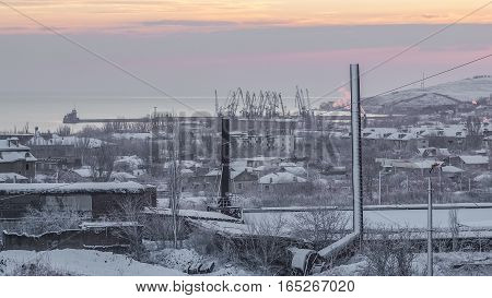 A snow-covered factory, the city and the morning