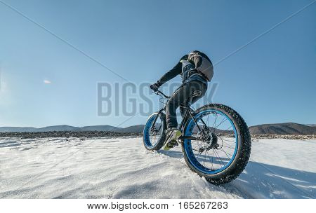 Fatbike also called fat bike or fat-tire bike - Cycling on large tire wheels. Cyclist goes to his bike on the frozen lake.
