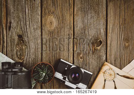 Accessories for travel top view on wooden background with copy space. Adventure and wanderlust concept image with travel accessories. Preparing for an exotic trip, journey and sightseeing.