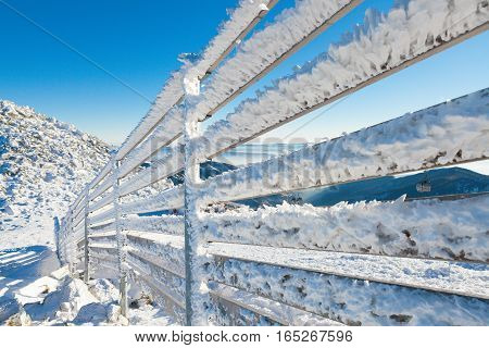 Fence Covered By Heavy Snow On A Sunny Winter Day After A Heavy Blizzard
