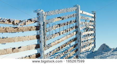 Fence Near Mountain Slope Covered By Heavy Snow On A Sunny Winter Day After A Heavy Blizzard