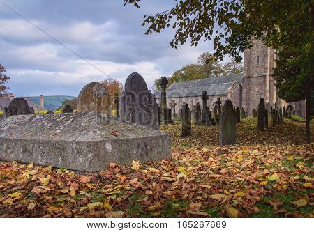 Graveyard near the church. Autumn. Fallen dry leaves lying on the ground. The clouds in the sky. Chagford. Dartmoor. Devon. UK