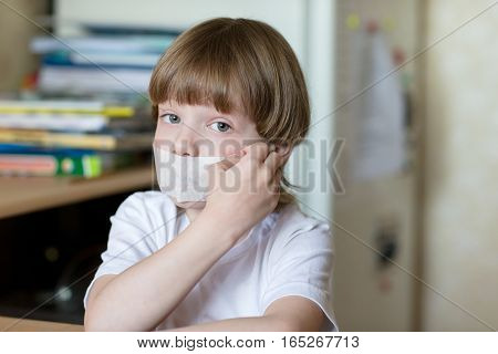 Offended child sits at a table with his mouth sealed with tape. The concept of domestic violence and child protection.