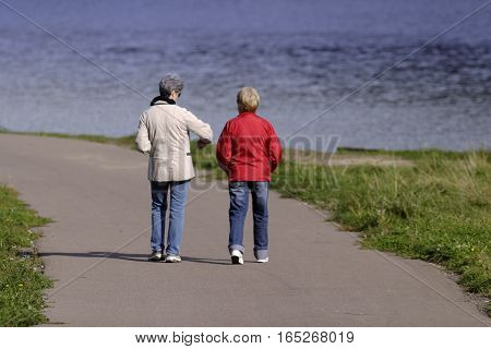 Two mature women walking near river back view