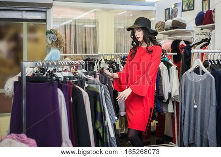 Beautiful young woman thinking what to dress near rack with hangers, shopping