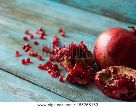 Organic pomegranate fruit on blue wooden background
