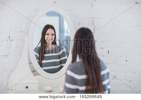 Portrait of elegant woman looking at reflection in mirror